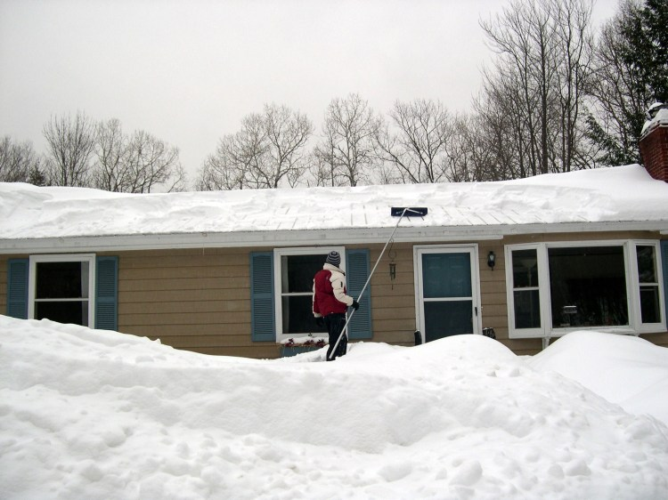 Raking snow off the house roof