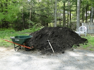 pile of loam with wheelbarrow and shovel