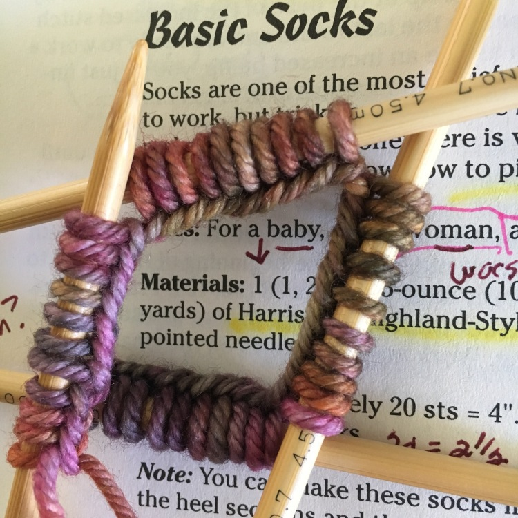 Using wood double-pointed needles to knit a sock.