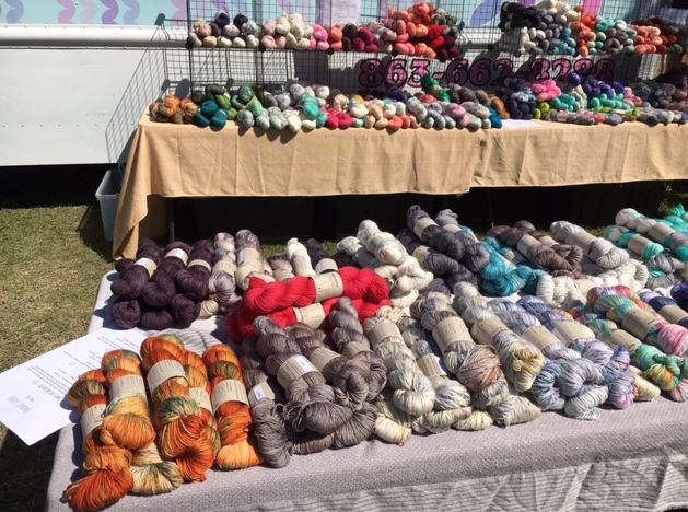 Tables of colorful yarn for sale set up on tables outside the Four Purl's yarn truck.
