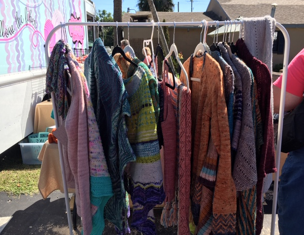 Rack of hand-knit shawls and sweaters