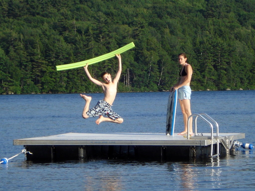 kids in summer on a raft at a lake swimming and playing