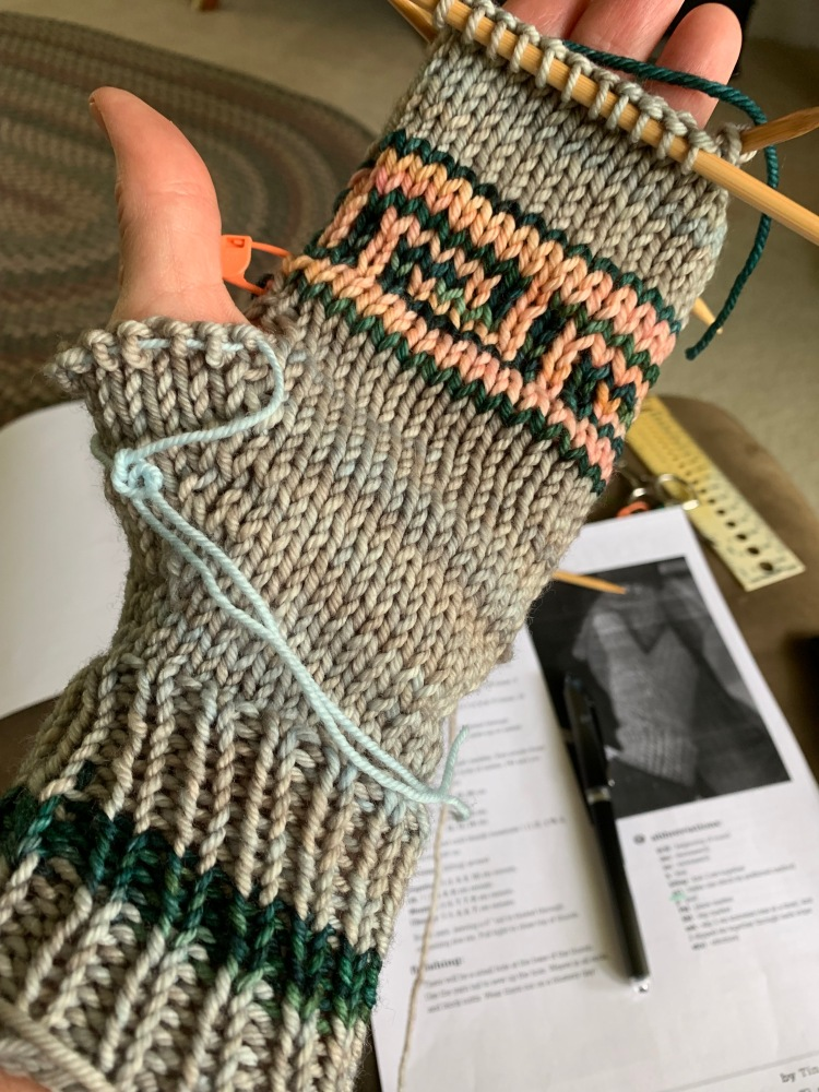 knitting mittens with thumb on hold with waste yarn to finish up fingers