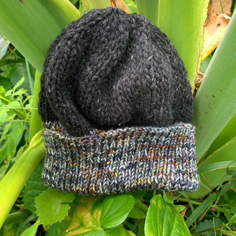Hand knitted winter hat in a tropical elephant ear plant