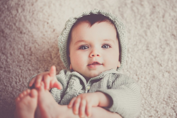 Baby in matching knitted hat and sweater