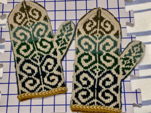 hand knit pair of mittens in Fiddlehead pattern