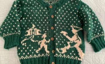 Old hand knit colorwork child's sweater with figures and house