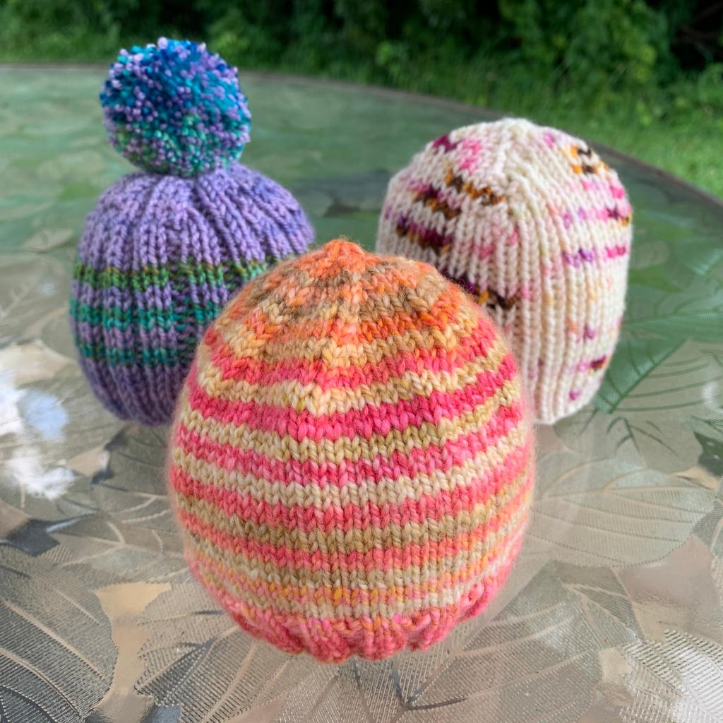 Three little hand-knit baby hats