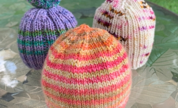 Three little hand-knit baby hats