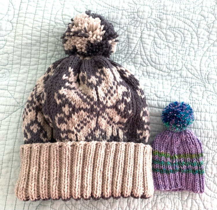 Two hand knit hats with pompoms