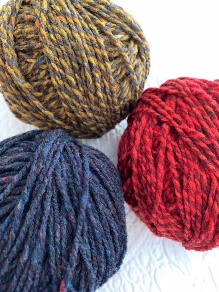 Brooklyn Tweed Shelter yarn in colors Old World, Amaranth, and Caraway
